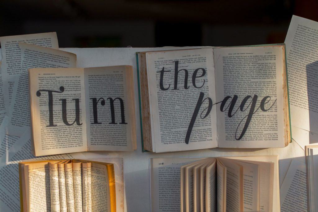 """Image of two open books with marker writing added to say """"Turn the page."""""""