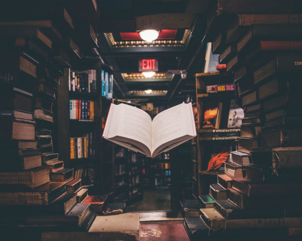 Photo of a book seeming to float between shelves.